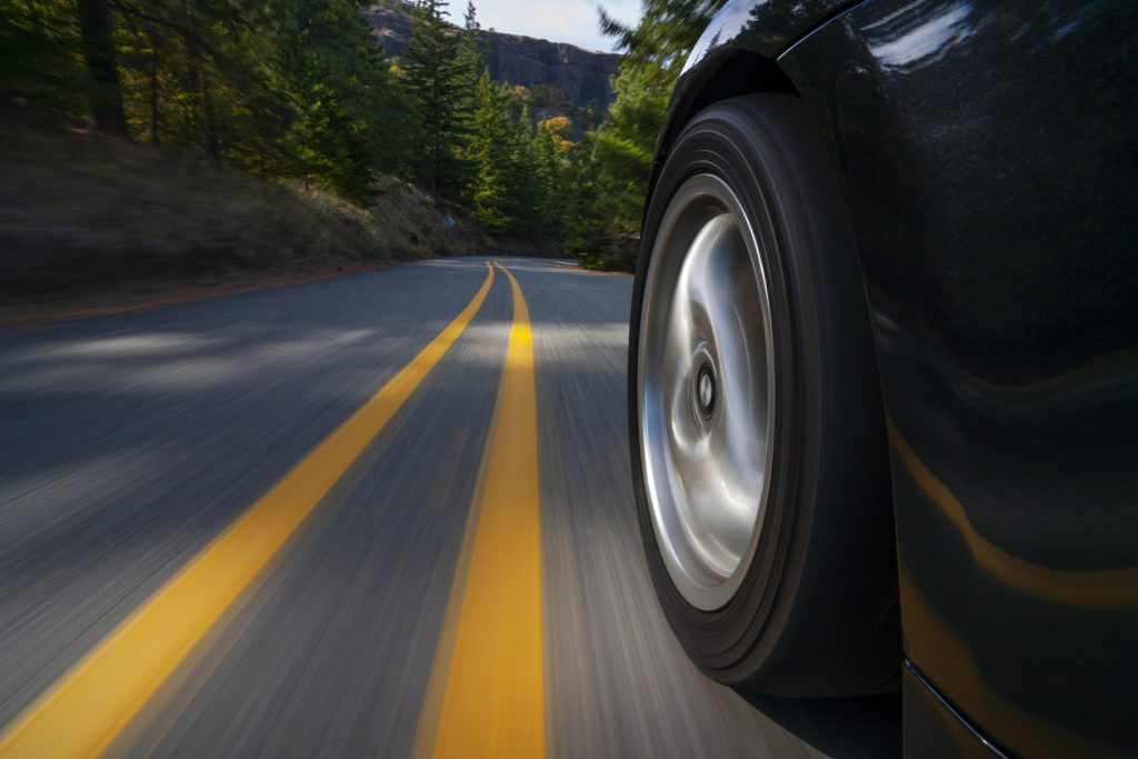 Close-up of a tire on a black car driving down a tree-lined street