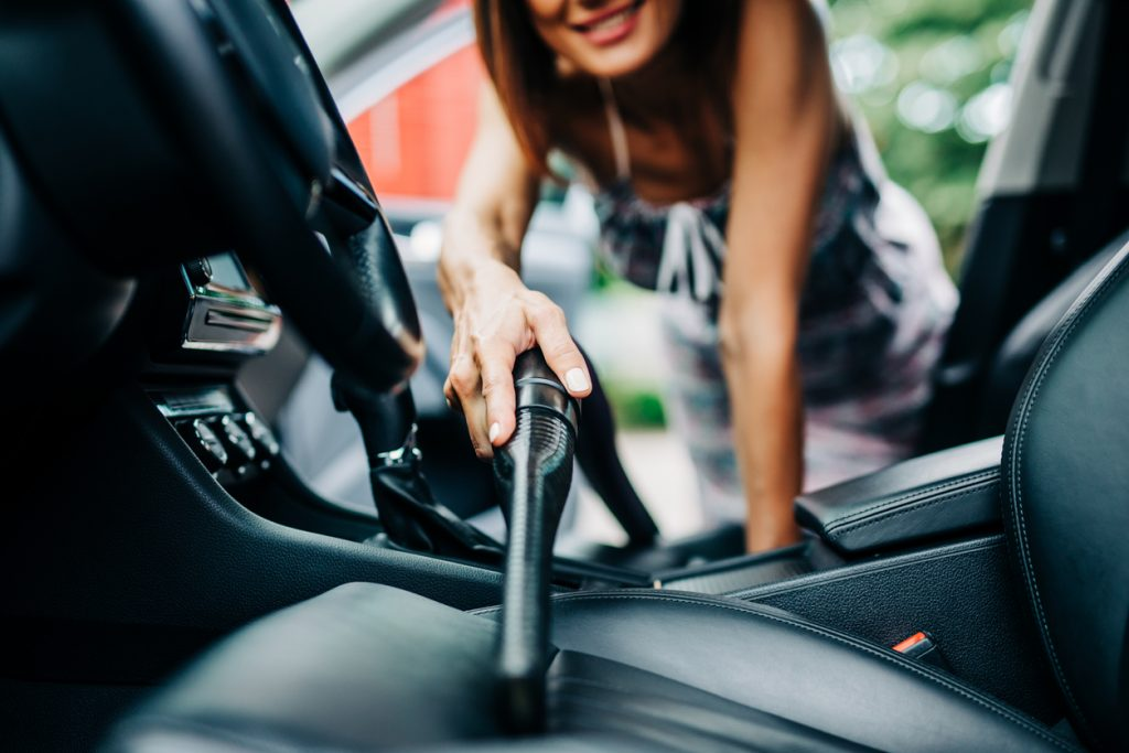 Happy woman cleans the interior of her car with vacuum cleaner.