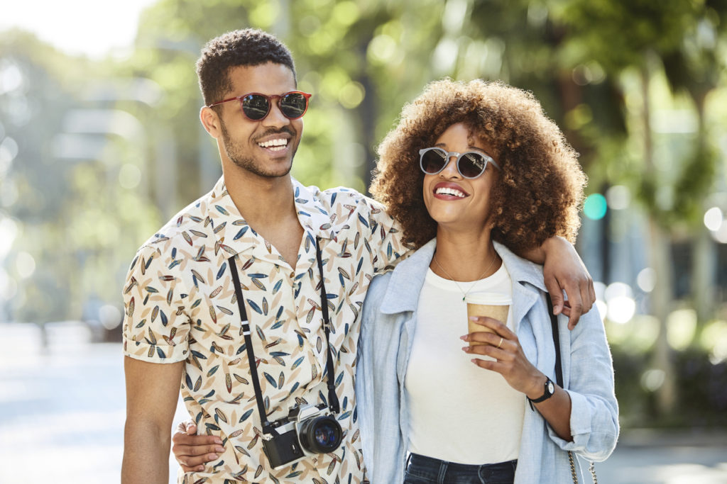 Smiling young couple walking arm in arm on sidewalk.