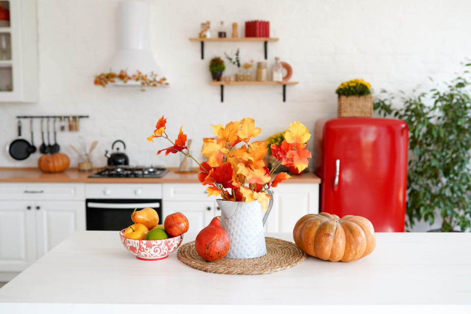 autumn table with vegetables in kitchen. red and yellow leaves in the vase and pumpkin on white background.