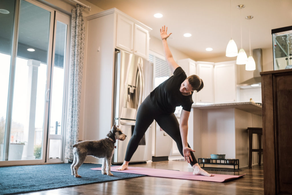 Woman Doing Home Fitness Exercises With Her Dog