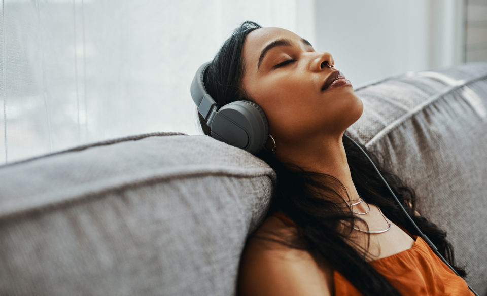 Young woman wearing earphones, listening to music on her couch