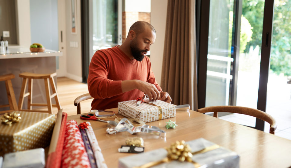 Shot of a young man wrapping Christmas presents at home