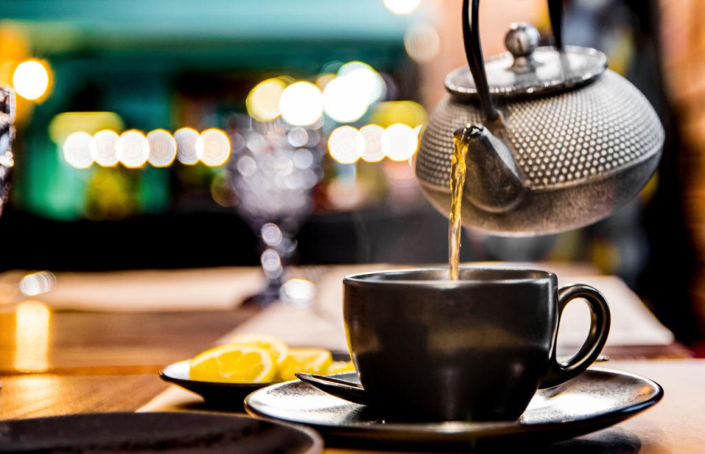 metal teapot pour black tea in black glass mug