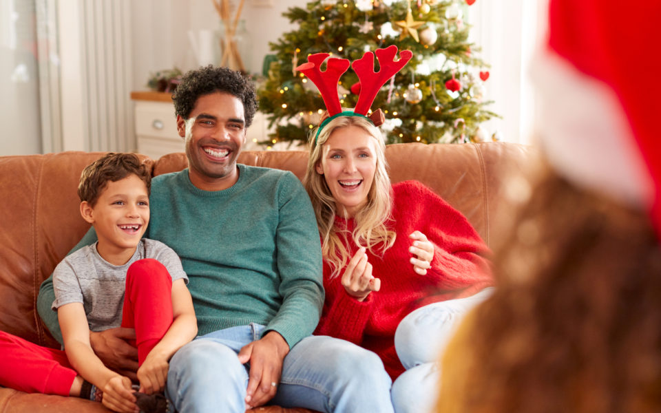 Family Sitting On Sofa Playing Game Of Charades At Christmas Together