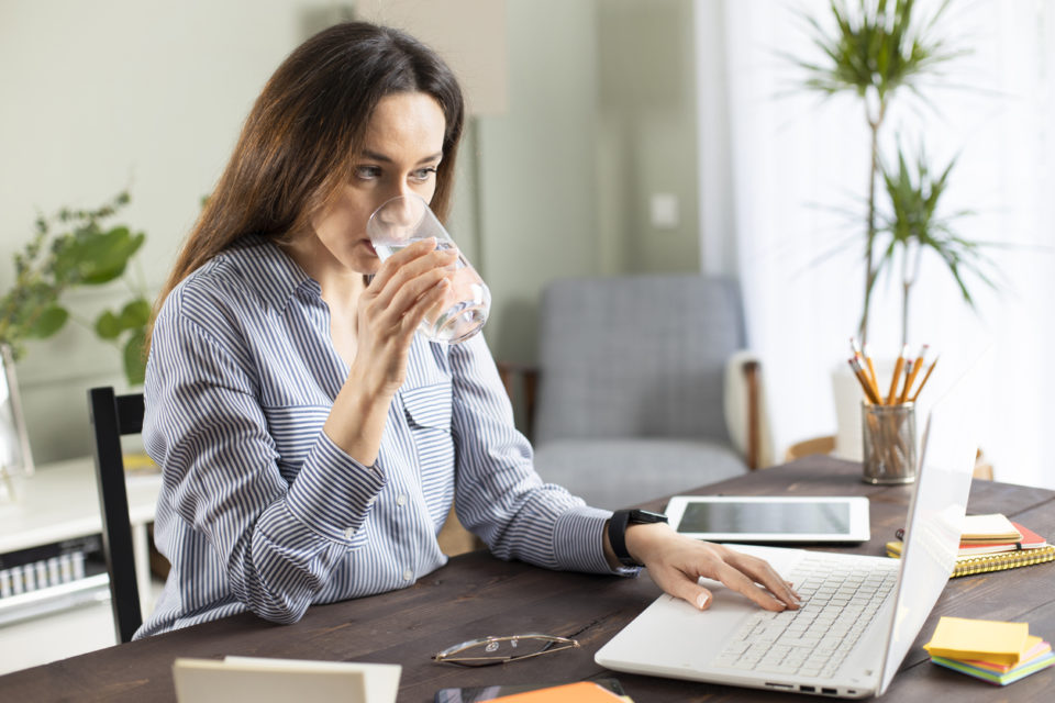 Young business woman working at home and drink glass of water. She drinking water while working at the laptop computer. Brown hair busy freelancer woman working at computer and connecting to the internet