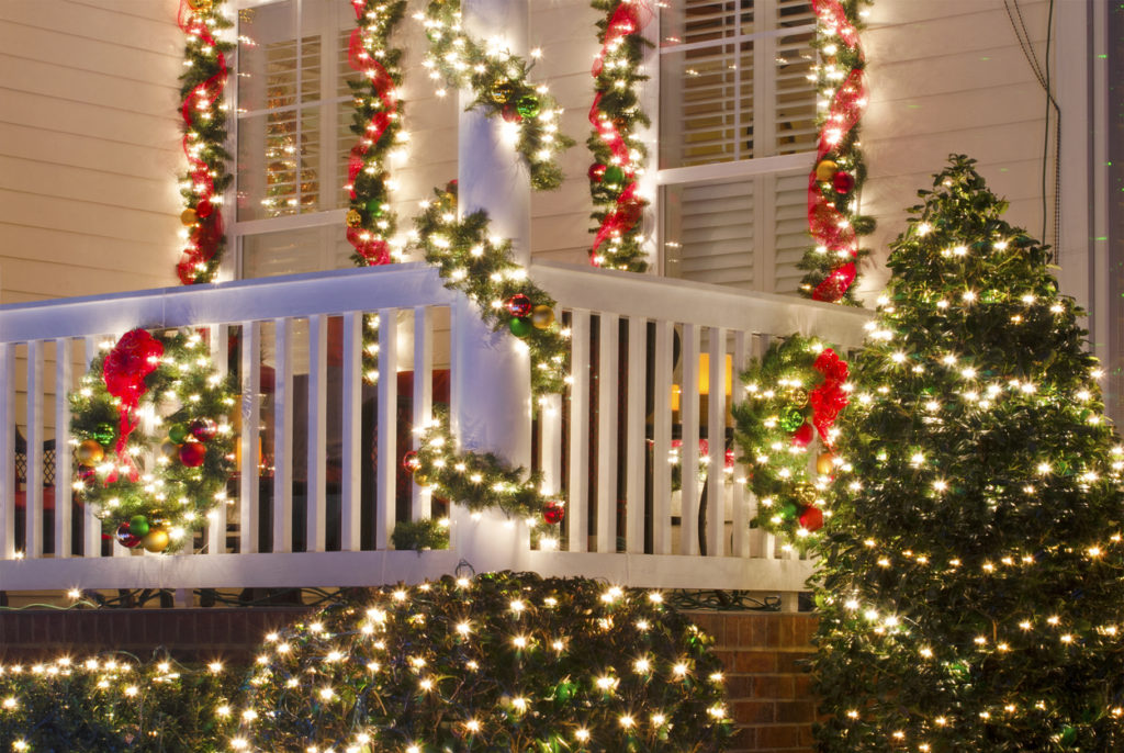White Christmas lights, garland, and red bows decorating the front porch of a house