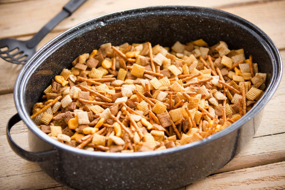 This is a shot of a party mix containing cereal, peanuts and pretzels in a roaster pan on an old wooden table.