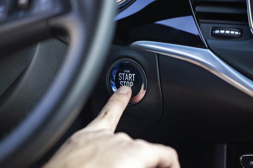 Man hand pressing car start and stop button.