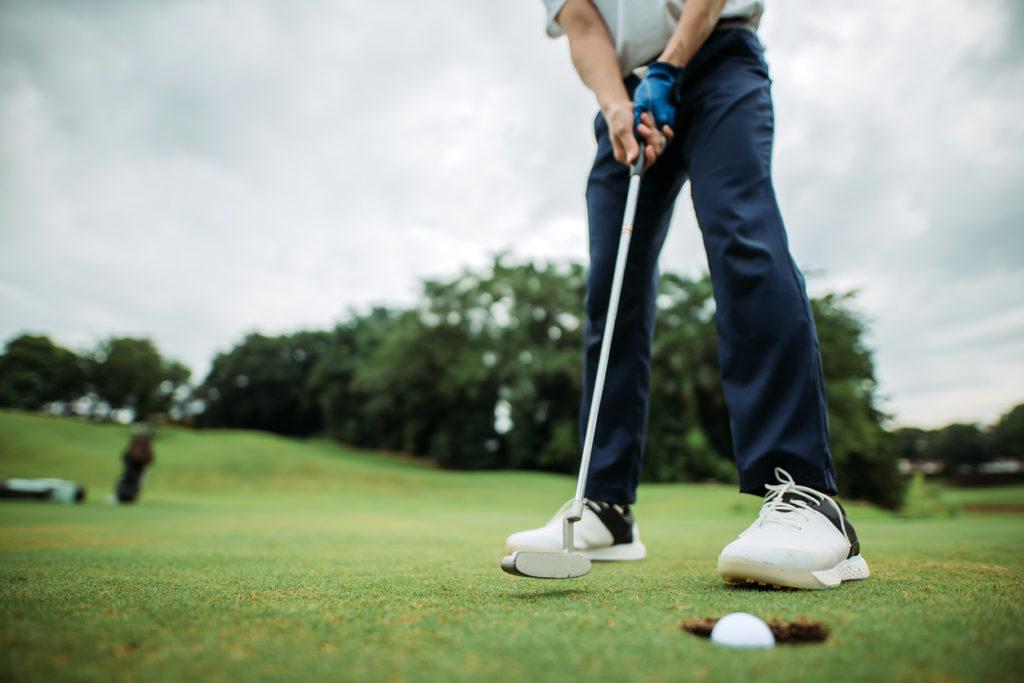 Man hitting golf ball on course