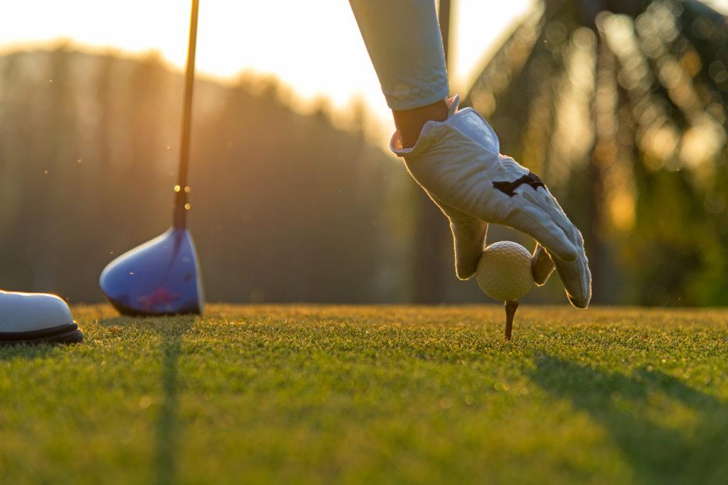 Golfer placing golf ball on the tee
