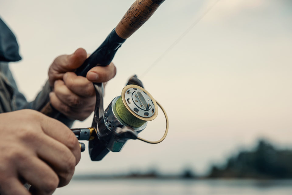 Fishing rod with a spinning reel in the hands of a fisherman.