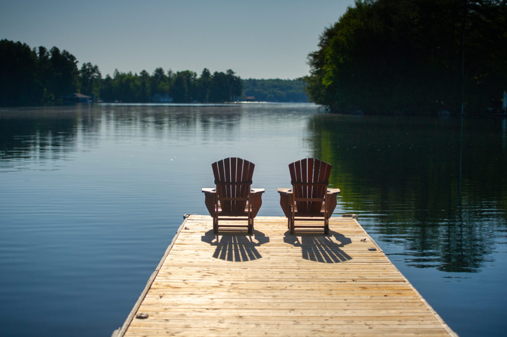 Two chairs sitting on a wooden pier facing the calm water