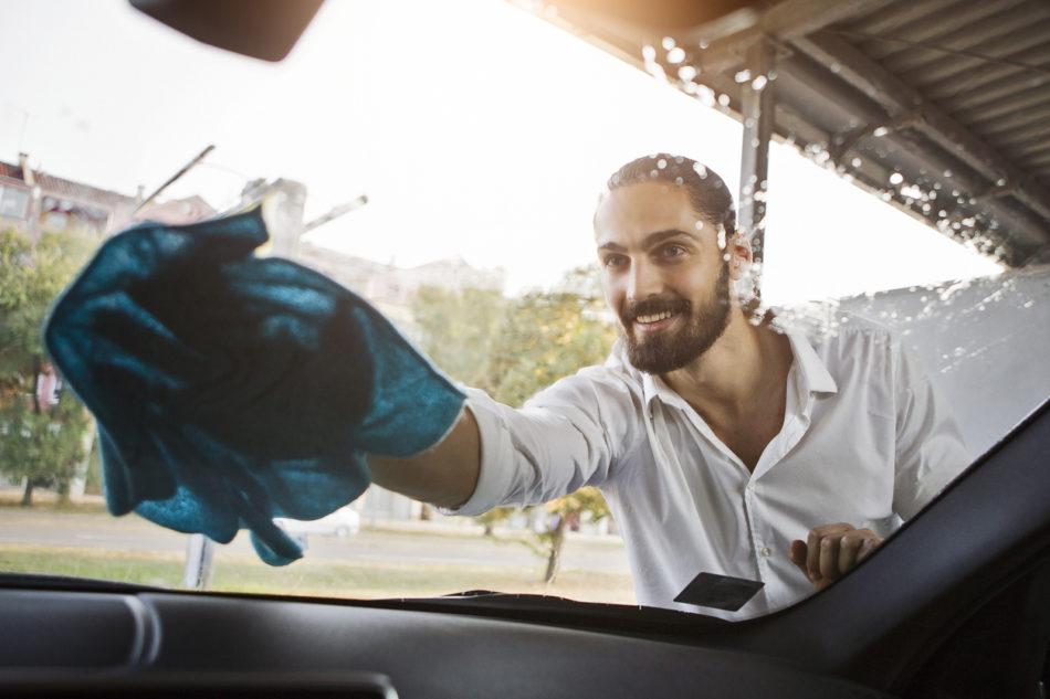 Young man washing windshield