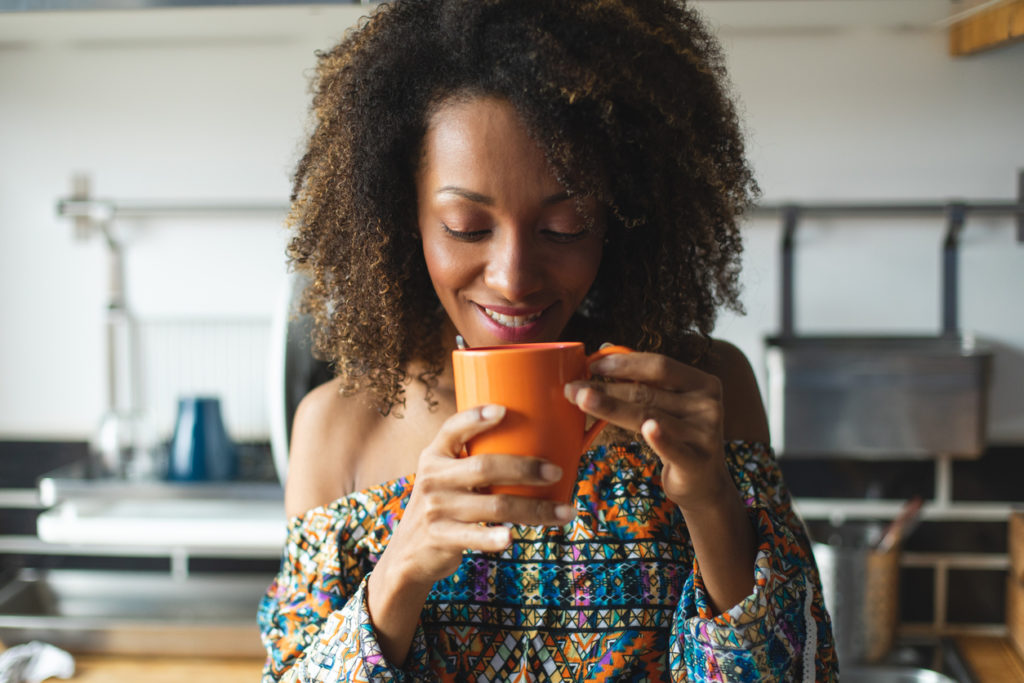 Woman drinking coffee in her home