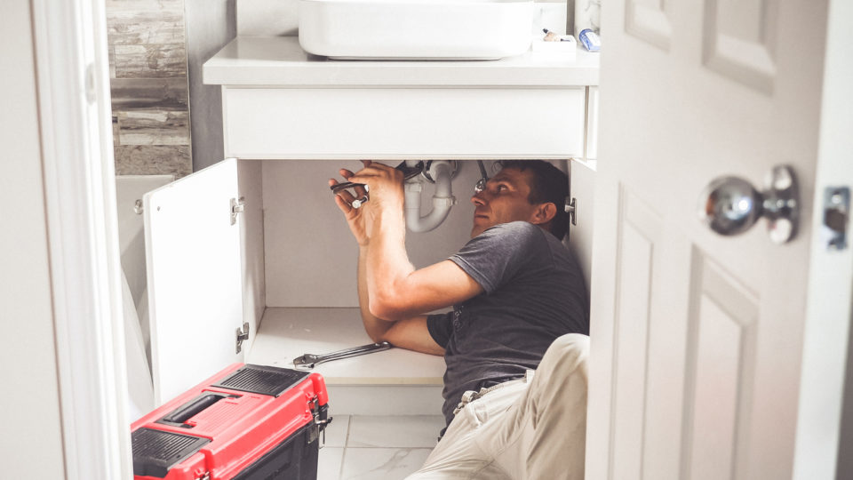 Plumber Man With Tools In the bathroom. Plumbing And Renovation