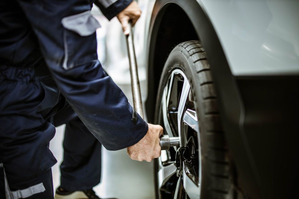 Close up of unrecognizable auto repairman using socket wrench while changing a tire in a workshop.