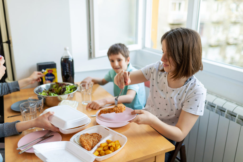 Children at the dining table at home taking from a box of take out food.