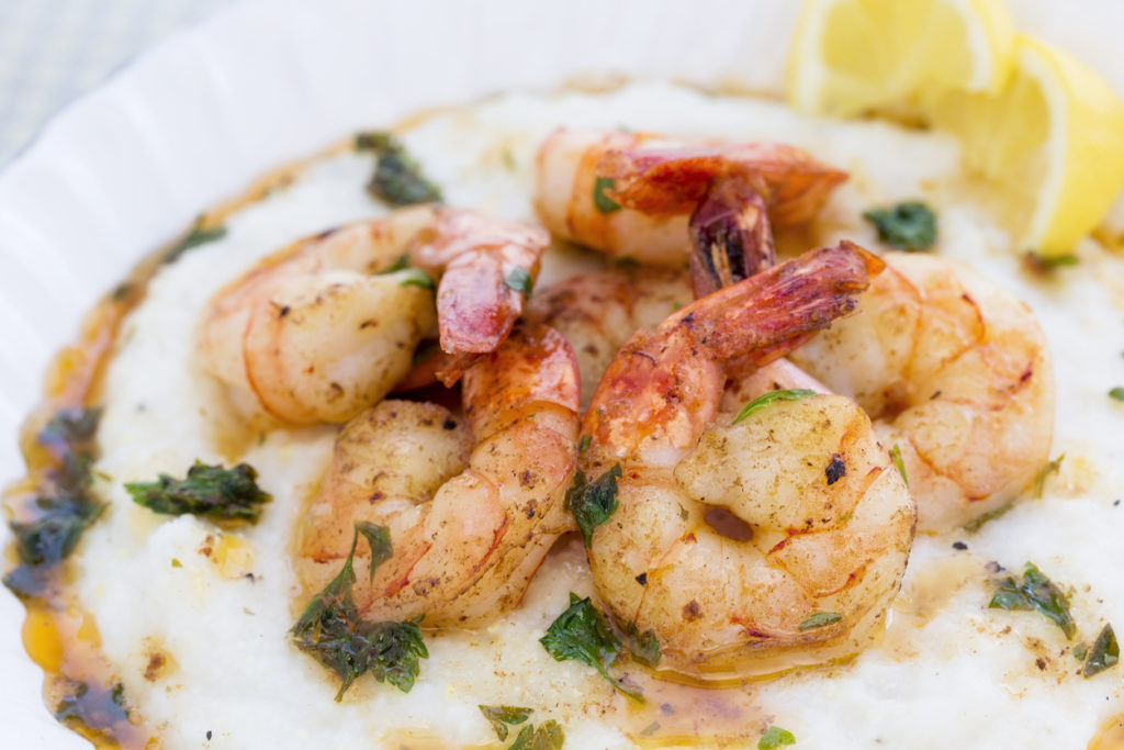 A hearty bowl of shrimp over buttery, savory grits.