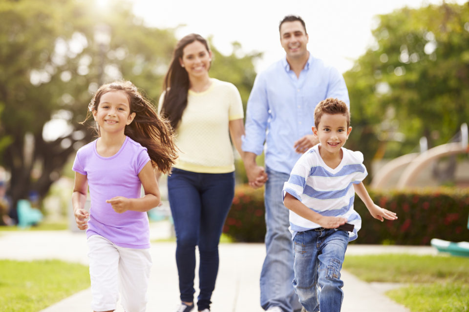 Family Walking In Park Together.