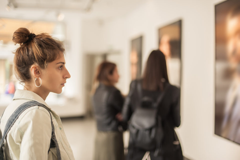 Group of woman looking at modern painting in art gallery.