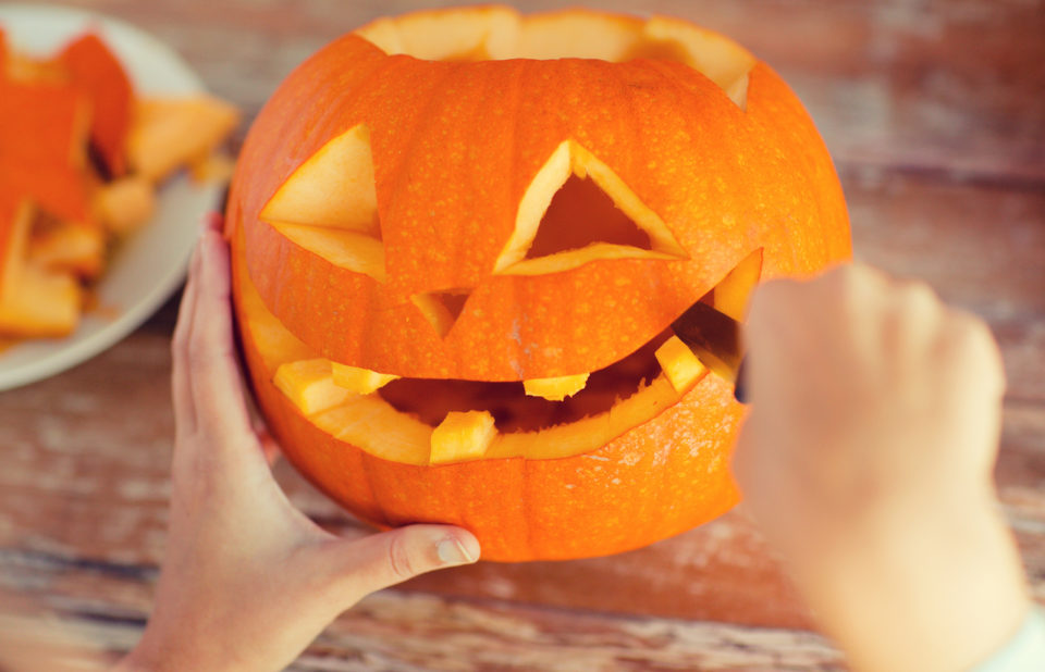 close up of woman's hands carving pumpkins at home