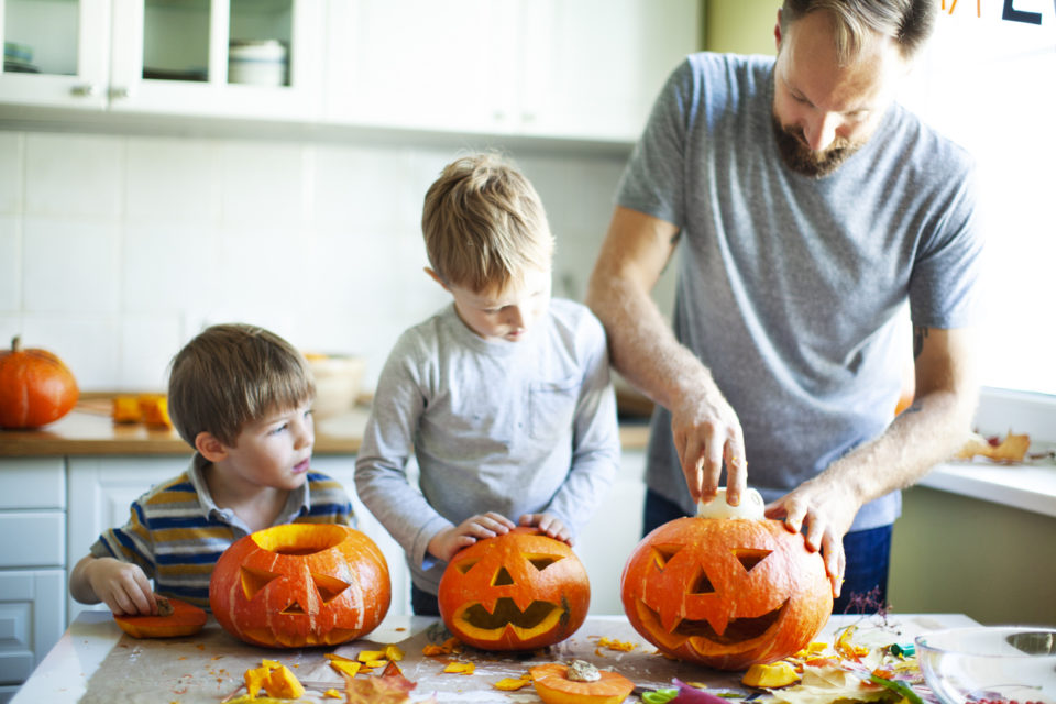 family carving pumpkins in kitchen