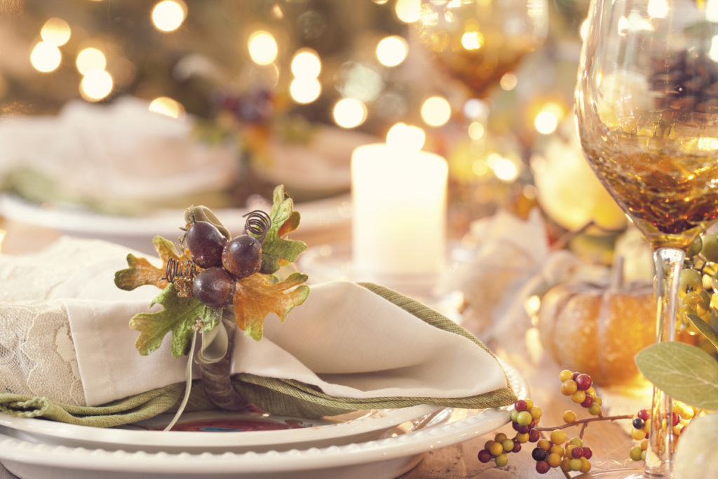 Thanksgiving holiday rustic dining table place setting with glowing candlelight