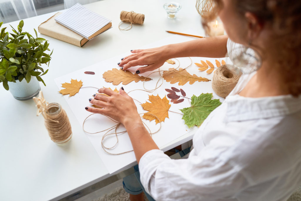 High angle portrait of young woman making handmade autumn decoration using yellow eaves