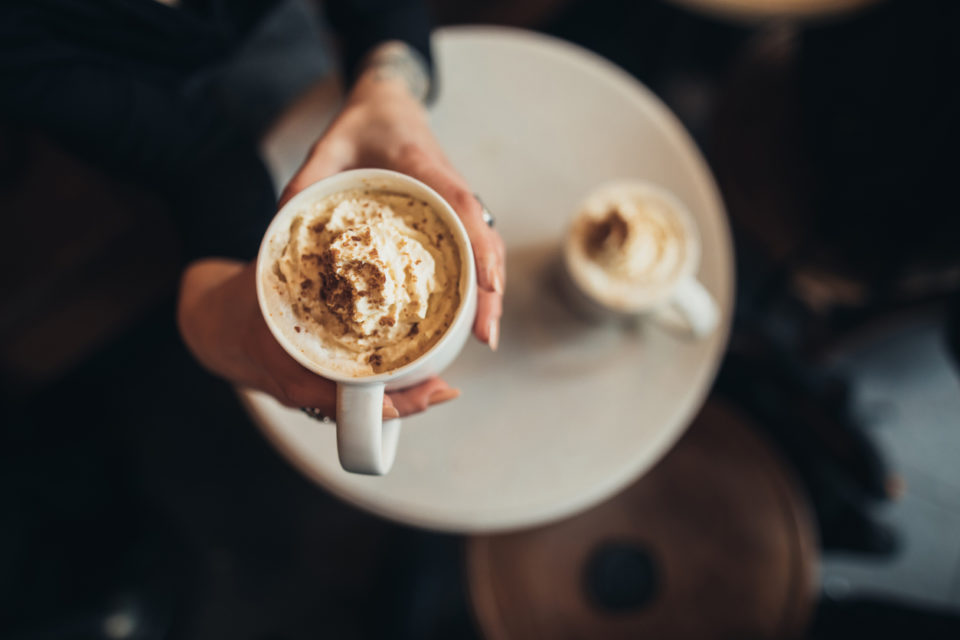 overhead shot of a latte with cream and cinnamon, with a white plate underneath