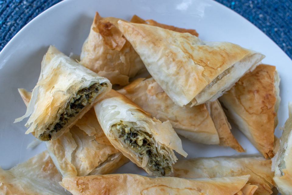Spanakopita Greek Spinach puff pastry pie triangles on white plate.
