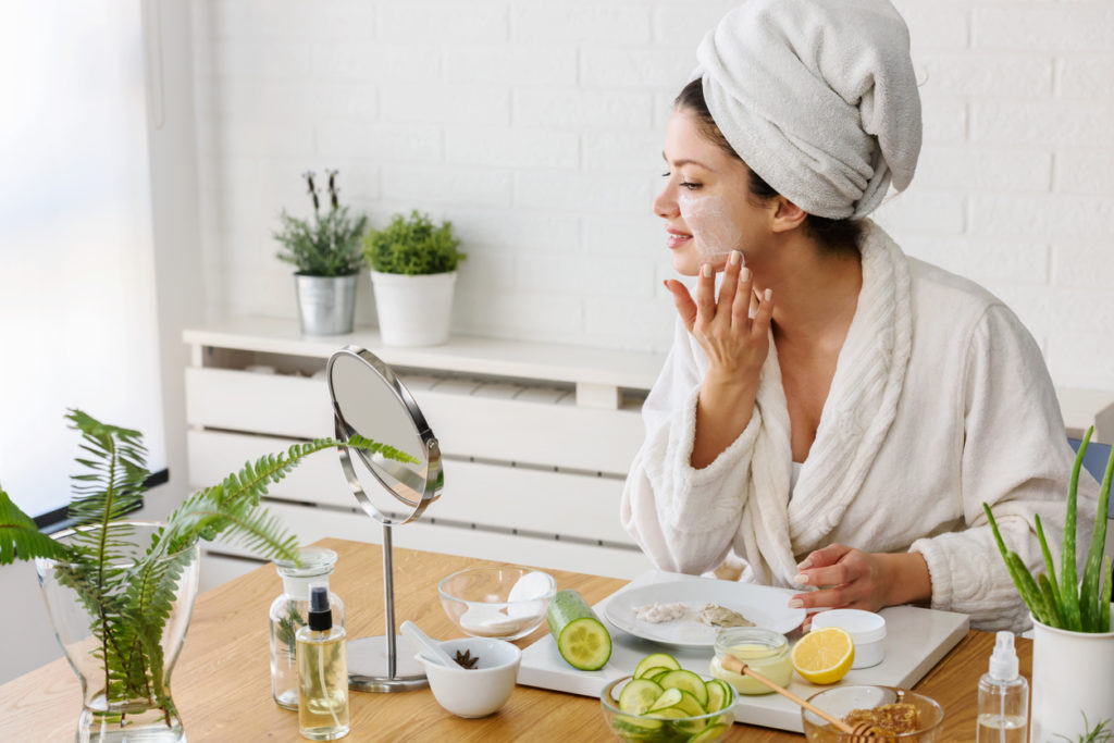 Young woman cleaning face with natural cosmetics. How to get clear and glowing skin. Portrait of young woman with clay face mask on wearing bathrobe. Homemade Face Mask