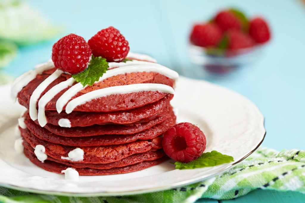Stack of red velvet pancakes with icing and raspberries