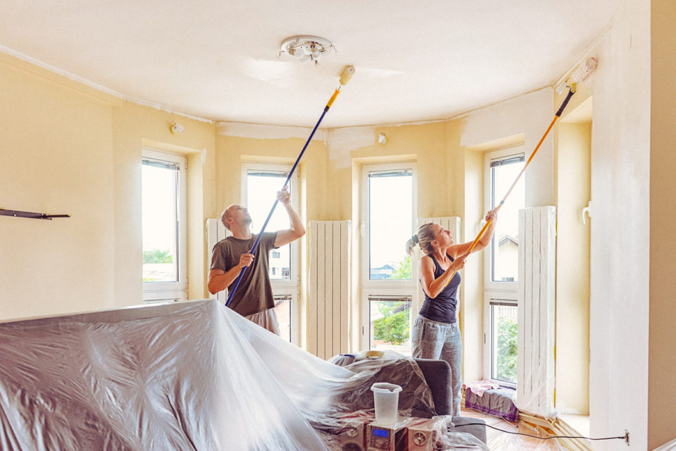 DIY home renovation work. Couple painting wall and ceiling with telescopic roller Man and woman in casual wear. The shot is executed with available natural light, and the copy space has been left.