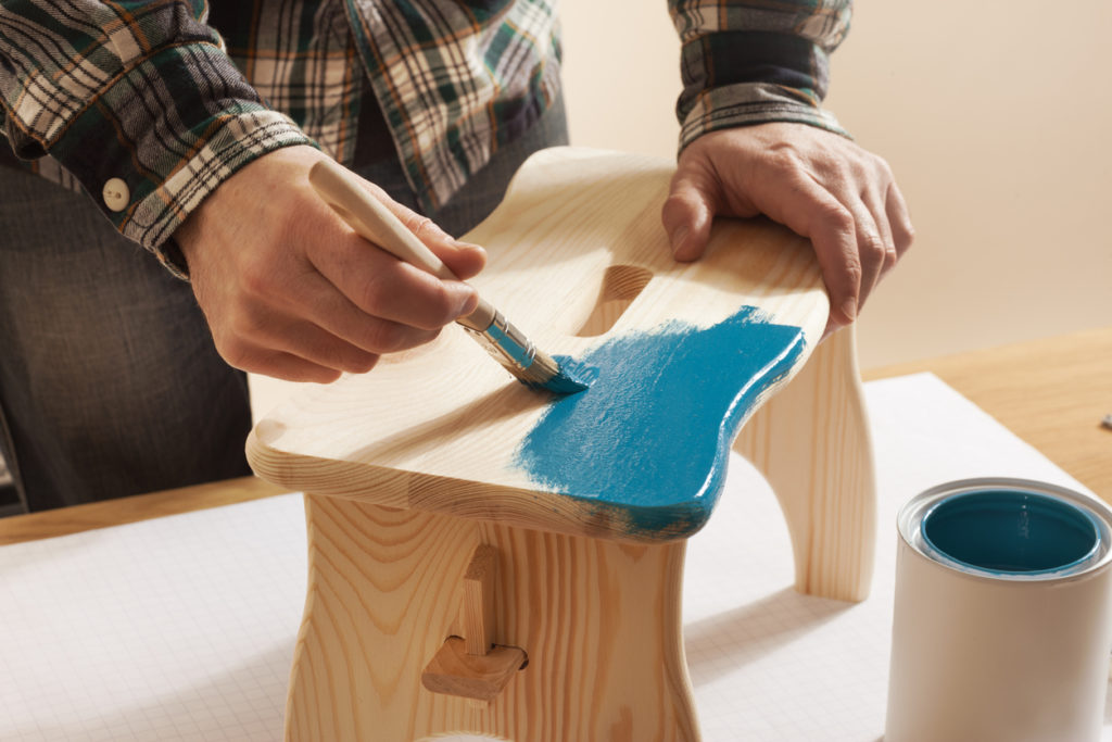 Craftsman varnishing a wooden handmade stool at home with a blue coating on a work table, hands close up