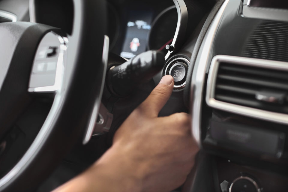 Finger pressing engine start button on car.