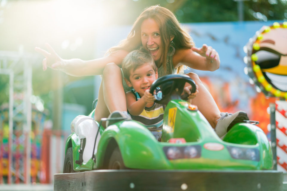 very happy mother and little son driving with toy car