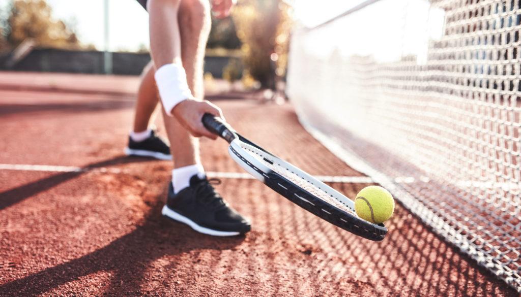 Young man playing tennis, close up photo.