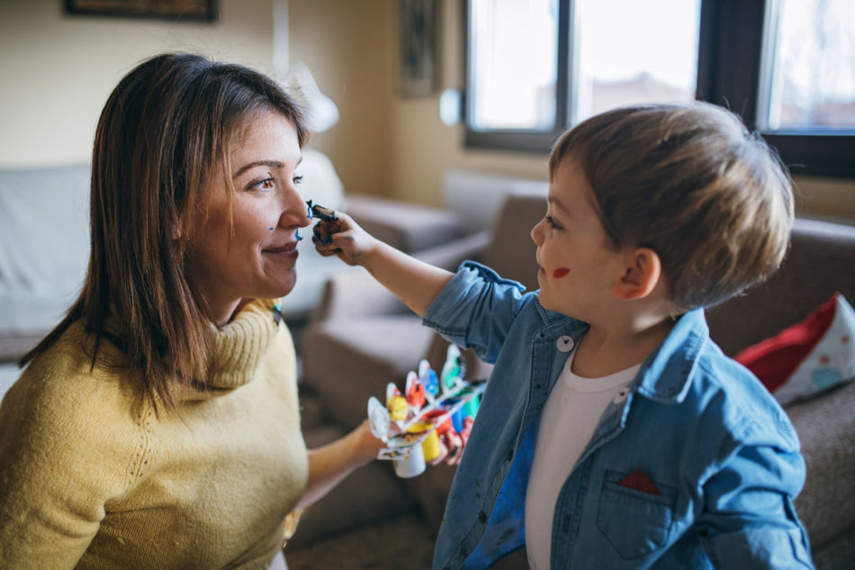 Little boy painting his pregnant mother with finger paint