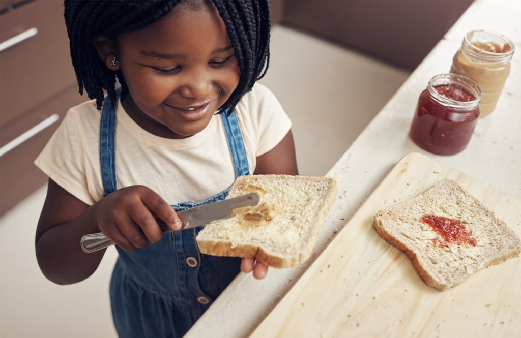 Cropped shot of an adorable little girl making lunch for herself in the kitchen at home